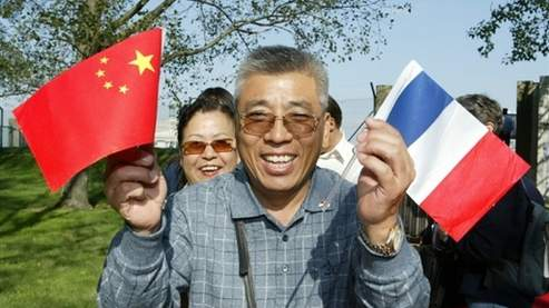 "les premiers touristes chinois ""officiels"" en provenance de Pékin brandissent des drapeaux francais et chinois, le 01 septembre 2004 à leur arrivée à l'aéroport de Roissy, pour une visite marathon de deux jours et demi, première étape d'un tour d'Europe de dix jours qui les conduira également en Suisse et en Italie. L'Union Européenne est devenue depuis le 1er septembre une ""destination autorisée"" par Pékin. Chinese tourist as part of the first Chinese nationals to visit the country with an official tour group brandishes the Chinese and French flag upon his arrival at Charles de Gaulle airport, outside Paris, 01 September 2004. The tourists will see the City of Light in grand style over the next two days going on a whirlwind tour that includes visits to the Louvre, the Eiffel Tower and the Versailles palace outside the capital and then will head to Switzerland and Italy."